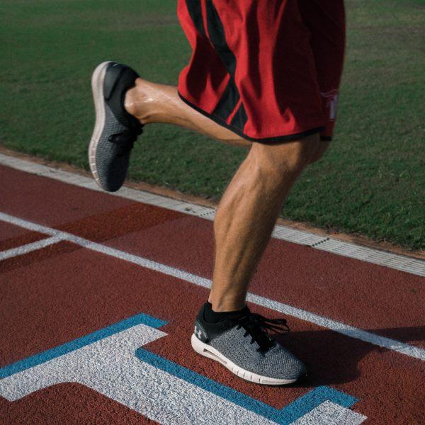 Piernas de corredor en pista de atletismo